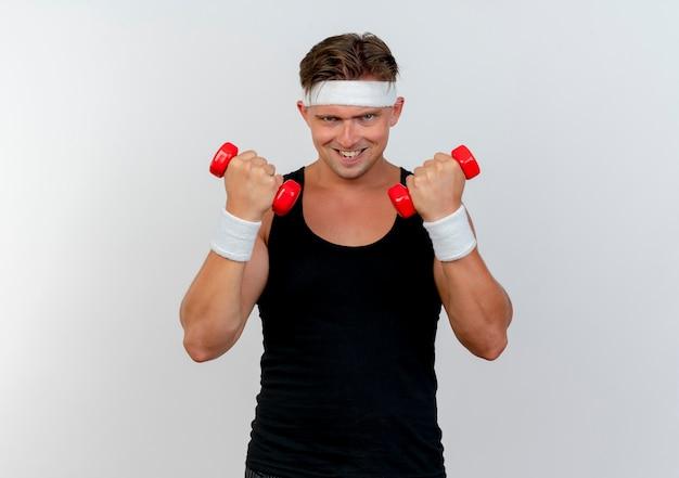 Przekonany, młody przystojny sportowy mężczyzna nosi pałąk i opaski na rękę podnosząc hantle na białym tle