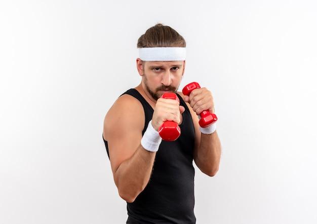 Przekonany, młody przystojny sportowy mężczyzna noszący opaskę i opaski, trzymający hantle i wykonujący gest bokserski na białym tle na białej ścianie z miejsca na kopię