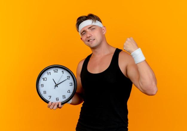 Przekonany, młody przystojny sportowy mężczyzna w opasce i opaskach na rękę, trzymając zegar i pięść zaciskającą na pomarańczowym tle