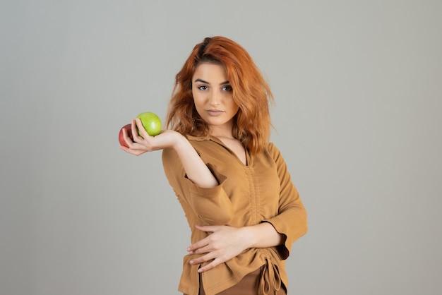 Przekonany, młody rudy, trzymając świeże jabłka i patrząc na kamery.