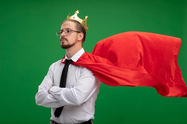 Przekonany, młody superbohater facet patrząc na bok noszenie korony i krawata skrzyżowane ręce na białym tle na zielono