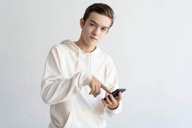 Przekonany, nastoletni facet reklamuje nową aplikację mobilną