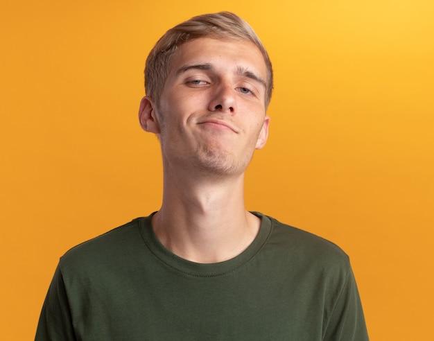 Przekonany, patrząc na przód młody przystojny facet na sobie zieloną koszulę na białym tle na żółtej ścianie