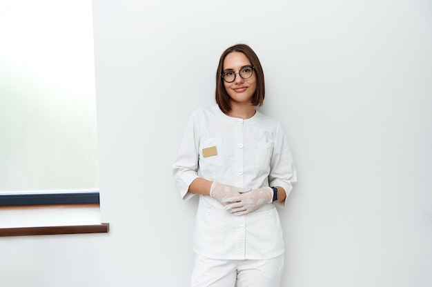 Przekonany, portret całkiem młoda lekarka, opierając się na białej ścianie w klinice. profesjonalny portret. międzynarodowy dzień lekarzy