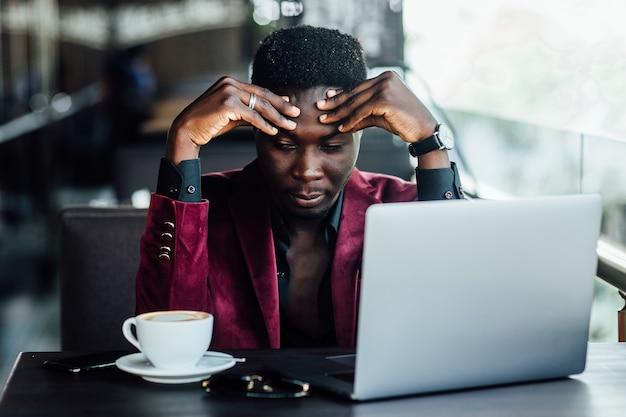 Przekonany, przedsiębiorca czytanie wiadomości finansowych na komputerze przenośnym podczas picia kawy na tarasie wygodnej restauracji hotelowej. poważny młody mężczyzna monitorowania informacji biznesowych.
