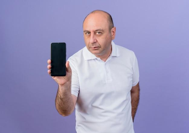 Przekonany, przypadkowy dojrzały biznesmen, pokazując telefon komórkowy, patrząc na kamery na białym tle na fioletowym tle z miejsca na kopię