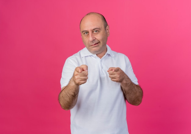 Przekonany, przypadkowy dojrzały biznesmen, robi ci gest na aparat na białym tle na różowym tle z miejsca na kopię