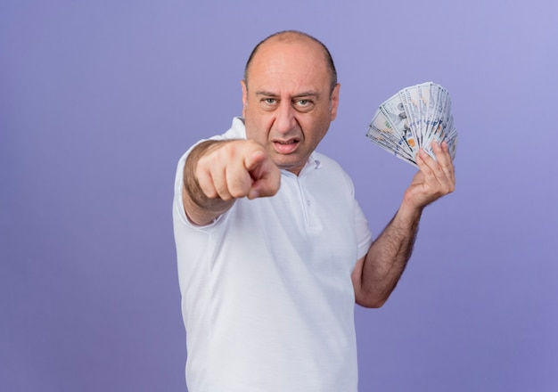 Przekonany, przypadkowy dojrzały biznesmen, trzymając pieniądze i wskazując na aparat na białym tle na fioletowym tle z miejsca na kopię