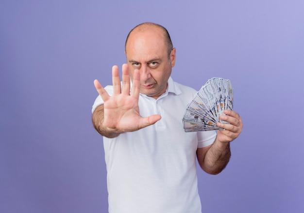 Przekonany, przypadkowy dojrzały biznesmen, trzymając pieniądze, wyciągając rękę w kierunku kamery i pokazując pięć ręką w aparacie na białym tle na fioletowym tle z miejsca na kopię