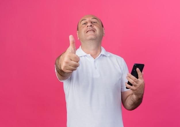 Przekonany, przypadkowy dojrzały biznesmen, trzymając telefon komórkowy i pokazując kciuk do góry na białym tle na różowym tle z miejsca na kopię