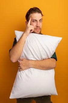 Przekonany, przystojny blondyn trzyma poduszkę i kładzie palec na świątyni odizolowanej na pomarańczowej ścianie