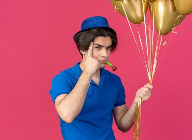 Przekonany, przystojny kaukaski mężczyzna w niebieskiej imprezowej czapce kładzie palec na skroni i trzyma balony z helem, wieje gwizdek imprezowy