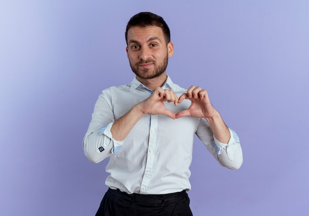 Przekonany, przystojny mężczyzna gestykuluje ręką znak serca na białym tle na fioletowej ścianie