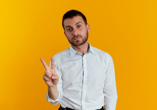 Przekonany, przystojny mężczyzna gestykuluje ręką znak zwycięstwa na białym tle na pomarańczowej ścianie