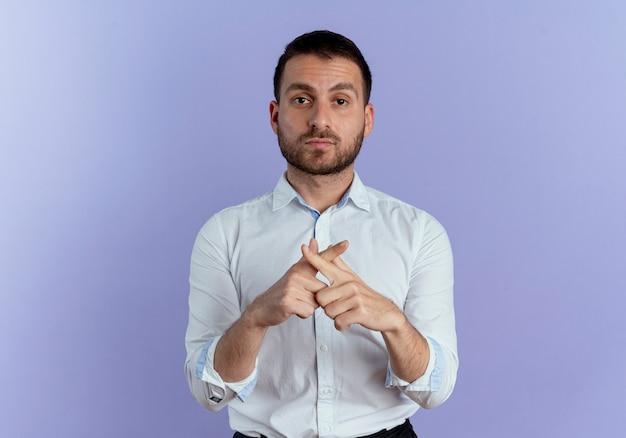 Przekonany, przystojny mężczyzna krzyżuje palce dwóch rąk gestykulacji żadnego znaku na fioletowej ścianie