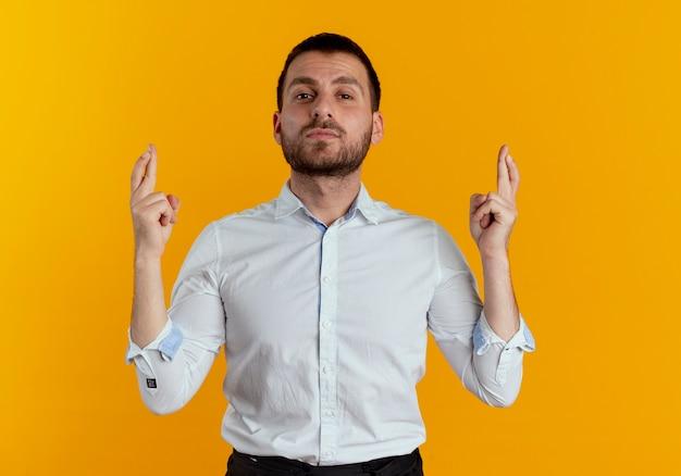 Przekonany, przystojny mężczyzna krzyżuje palce na białym tle na pomarańczowej ścianie