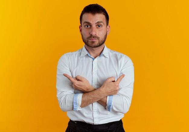 Przekonany, przystojny mężczyzna krzyżuje ręce, wskazując na boki na białym tle na pomarańczowej ścianie