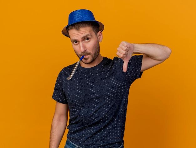 Przekonany, przystojny mężczyzna ubrany w niebieski kapelusz strony kciuki w dół dmuchanie gwizdkiem na białym tle na pomarańczowej ścianie z miejsca na kopię