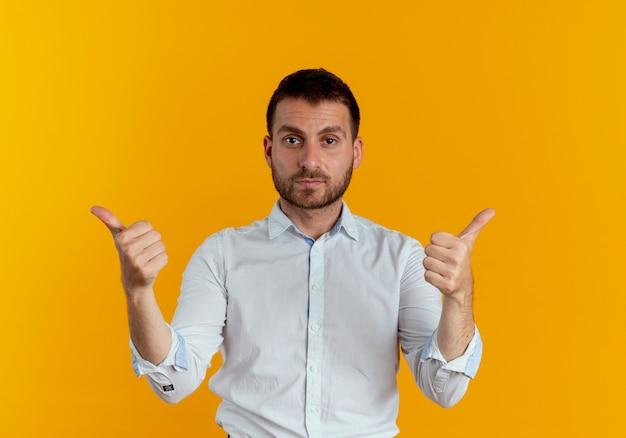 Przekonany, przystojny mężczyzna wskazuje na bok rękami odizolowanymi na pomarańczowej ścianie