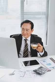 Przekonany, starszy lider azjatyckiego biznesu, siedząc przy biurku.