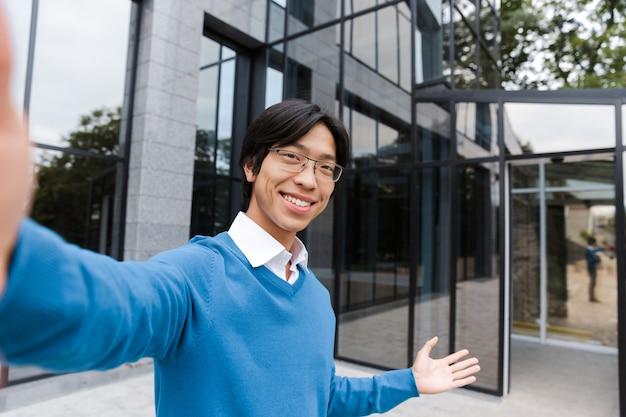 Przekonany, uśmiechnięty biznesmen azjatycki, biorąc selfie przed szklanym budynkiem na zewnątrz