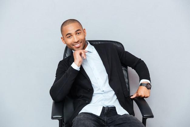 Przekonany, uśmiechnięty młody człowiek z afryki, siedzący na krześle biurowym