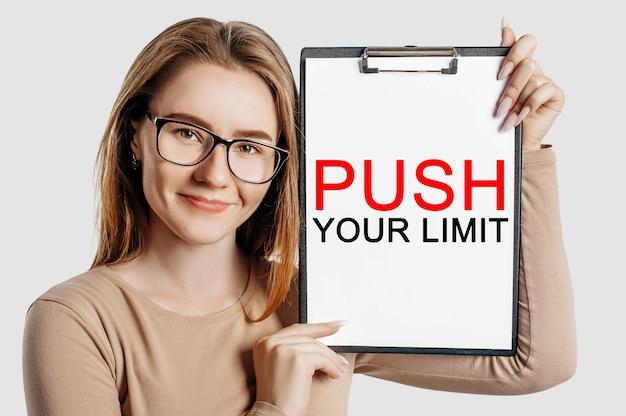 Przekraczaj swoje ograniczenia. piękna młoda biznesowa kobieta w okularach trzyma schowek z makiety miejsca na białym tle na szarym tle