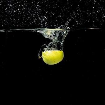 Przekrawające zielone jabłko rozpryskiwania w czystej wodzie