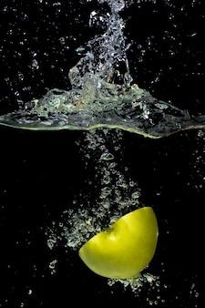 Przekrawające zielone jabłko spada do wody z pluskiem i bańki