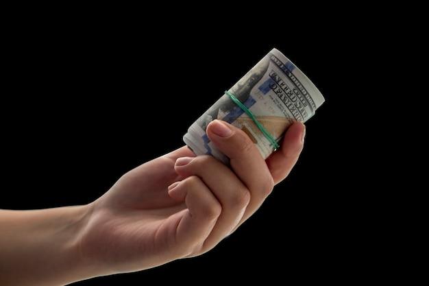 Przekręciłem 100-dolarowe banknoty w ręku. koncepcja sukcesu w biznesie.