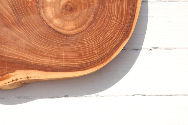 Przekrój drzewa leży na białej drewnianej powierzchni, widok z góry