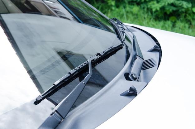 Przekrój przodu białego pojazdu i jego maski przedniej szyby i wycieraczek.