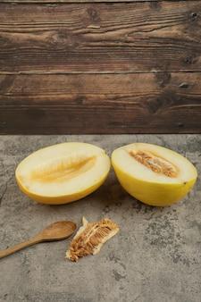 Przekrój pyszne żółte melony na pół na marmurowej powierzchni drewnianą łyżką.