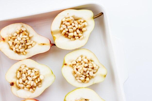 Przekrojone na pół dojrzałe gruszki nadziewane orzechami i miodem w białym naczyniu do pieczenia