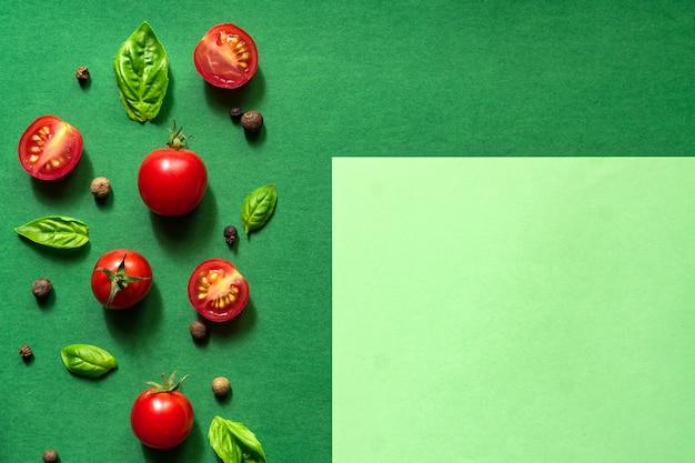 Przekrojone soczyste pomidory czereśniowe i liście bazylii. koncepcja zdrowego odżywiania. widok z góry. skopiuj miejsce