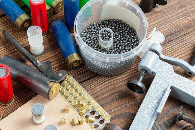 Przeładowanie pocisków strzelbowych przy użyciu specjalnego wyposażenia. proszek, kule, frakcja, łuski, śrut na podłoże drewniane.