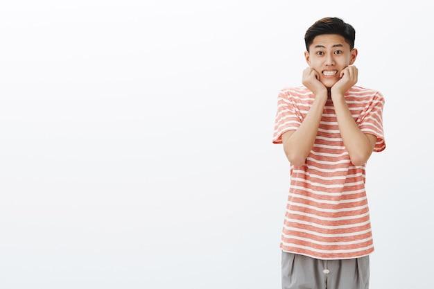 Przeładowanie słodyczą. portret głupi atrakcyjny miły azjatycki facet z ciemnymi krótkimi włosami, uśmiechając się szeroko, opierając twarz na dłoniach w efektownej kobiecej pozie