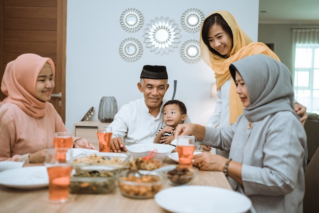 Przełamywanie postu. muzułmanin azjatykci z hidżabem jedzą razem kolację iftar w domu, siedząc na stole