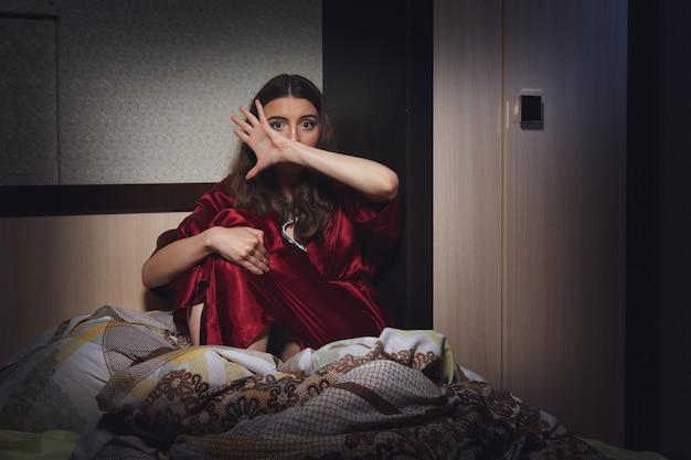 Przelękła desperacka kobieta w sypialni. przemoc społeczna.
