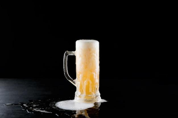 Przelewający się kubek świeżego zimnego piwa