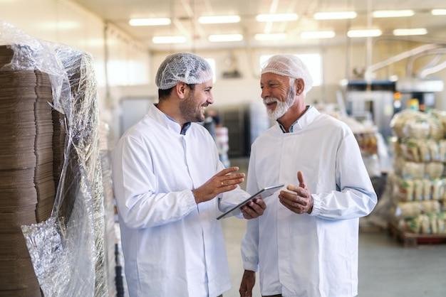 Przełożony rozmawia z pracownikiem trzymając tablet. oboje ubrani w mundury. wnętrze fabryki żywności.