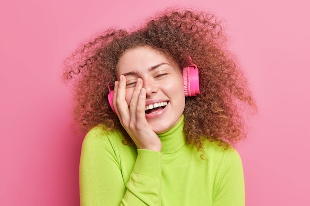 Przemęczona nastolatka z kręconymi, krzaczastymi włosami uśmiecha się szeroko trzyma rękę na twarzy zamyka oczy z przyjemności słucha muzyki przez bezprzewodowe słuchawki ubrana niedbale odizolowana na różowej ścianie