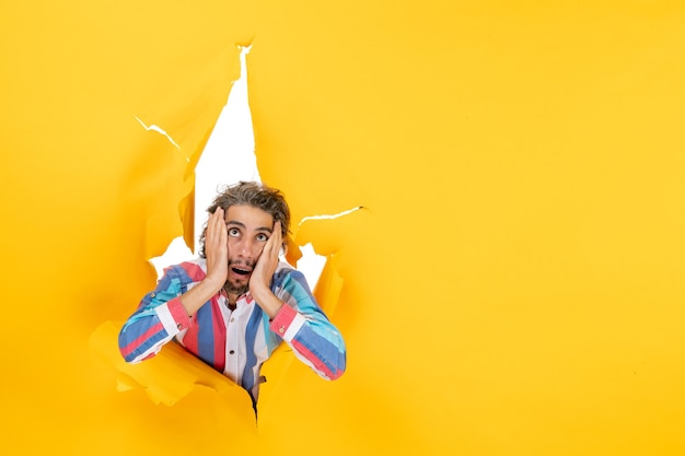 Przemęczony i emocjonalny młody facet pozuje do kamery przez rozdartą dziurę w żółtym papierze