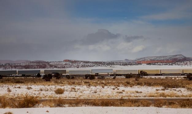 Przemieszczanie długiego pociągu kontenerowego wzdłuż torów kolejowych, transport i dostarczanie towarów przez pustynię w arizonie.