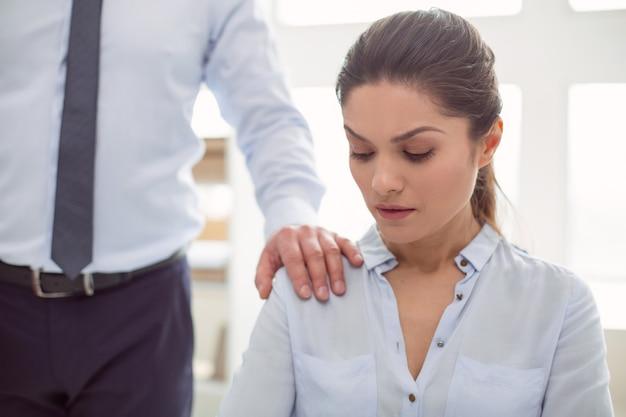 Przemoc wobec kobiet. miła, smutna, nieszczęśliwa kobieta siedzi w biurze i patrzy na męską dłoń podczas molestowania seksualnego