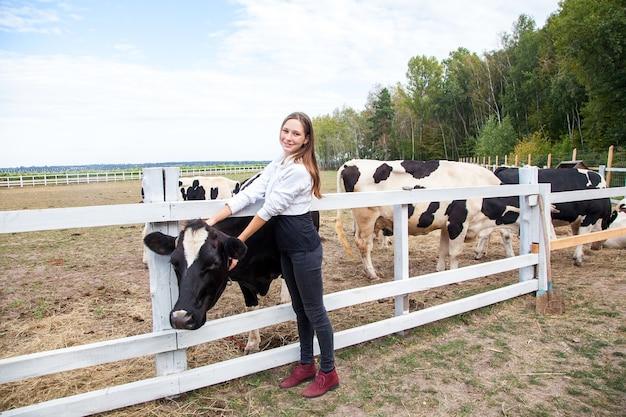 Przemysł rolniczy, rolnictwo, koncepcja hodowli ludzi i zwierząt. młoda kobieta i krowy w oborze na farmie mlecznej. na wolnym powietrzu