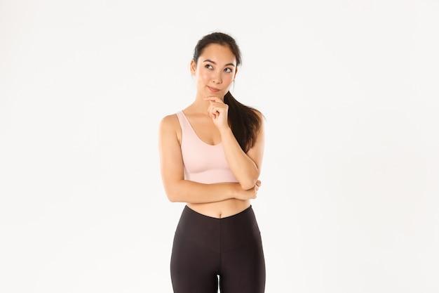 Przemyślana azjatycka dziewczyna fitness, lekkoatletka myśli nad nowymi ćwiczeniami, odwracając wzrok, zastanawiając się, dokonując wyboru, białe tło.