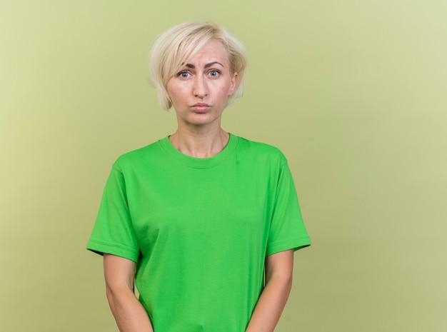Przemyślana blondynka słowiańska blondynka w średnim wieku patrząc na kamery na białym tle na oliwkowym tle z miejsca na kopię