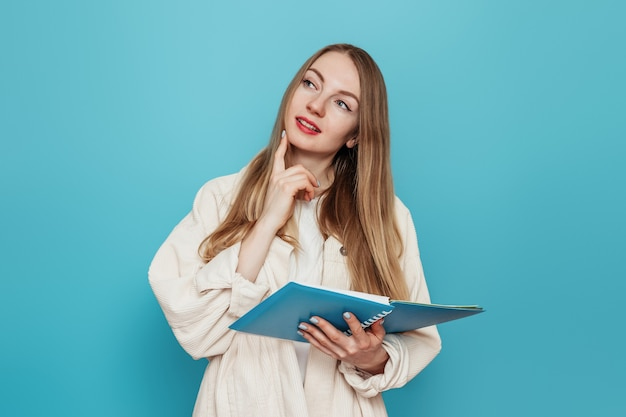 Przemyślana blondynka studentka trzyma otwarty zeszyt i chce skopiować miejsce na białym tle na niebieskiej ścianie