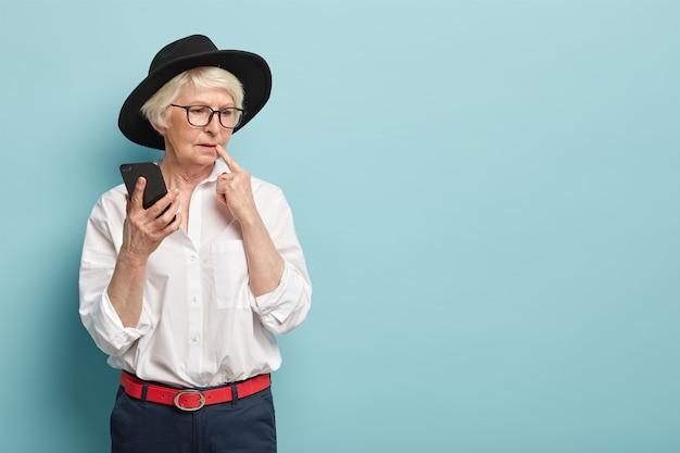 Przemyślana, charyzmatyczna seniorka ubrana w modny strój, myśli o treści wiadomości, trzyma w ręku nowoczesny telefon komórkowy